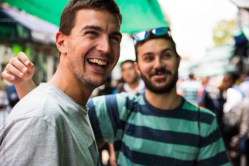 Two young happy male friends having fun in a street market  by Alejandro Moreno de Carlos for Stocksy United