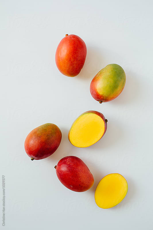 whole and cut mangoes by Christine Han for Stocksy United