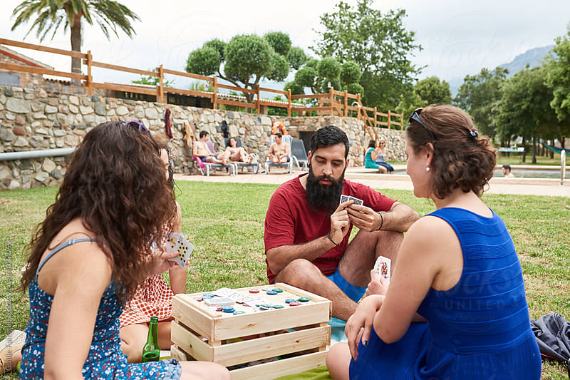Friends playing poker game in garden by Guille Faingold for Stocksy United
