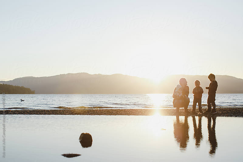 Young mom and kids enjoying the ocean beach at sunset by Rob and Julia Campbell for Stocksy United
