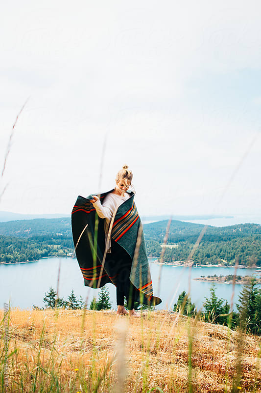 Young Blonde Woman Wrapping Wool Blanket Around Herself On Forest Island Hillside by Luke Mattson for Stocksy United