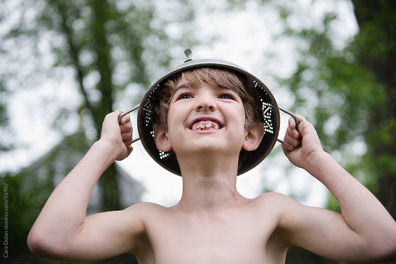 Smiling boy wears colander on his head while playing in his yard by Cara Dolan for Stocksy United