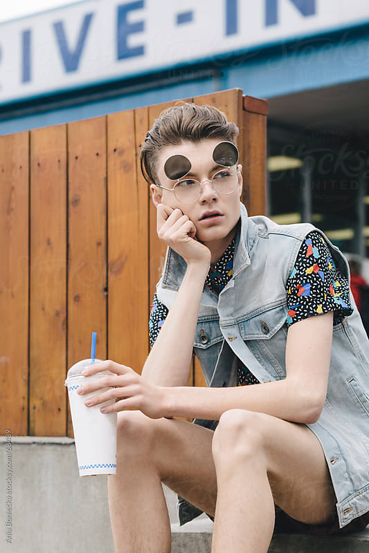 Trendy young hipster in sunglasses holding a milkshake cup by Ania Boniecka for Stocksy United