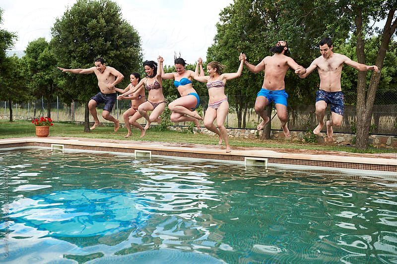 Group of friends jumping in swimming pool by Guille Faingold for Stocksy United