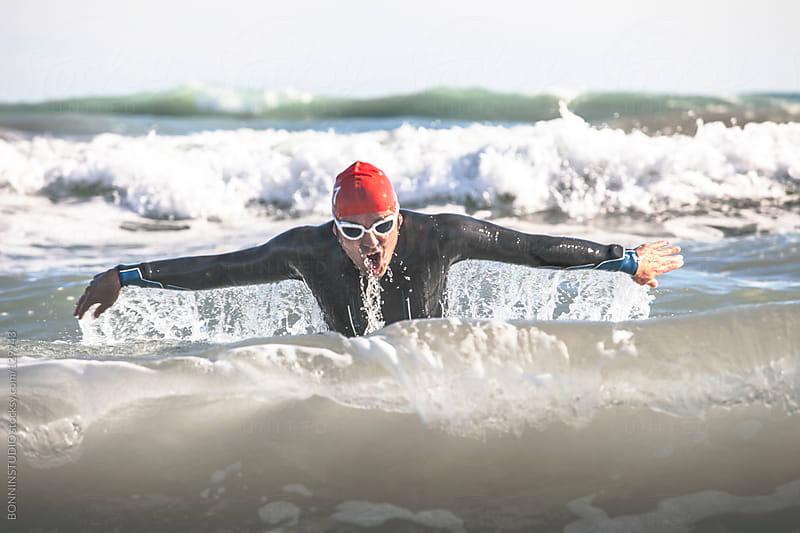 Triathlete swimming on the sea. Triathlon race. by BONNINSTUDIO for Stocksy United
