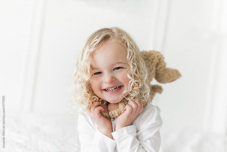 Simple close up of smiling young girl with blond curly hair by Amanda Worrall for Stocksy United