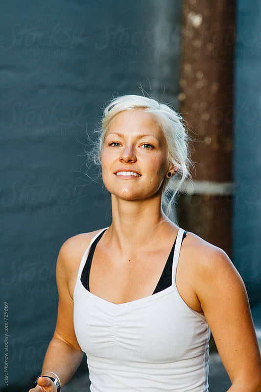 portrait of vibrant young female exercising in urban city alley by Jesse Morrow for Stocksy United