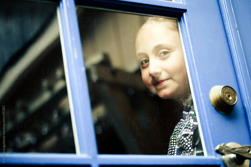 Ltitle girl smiling and looking through the glass door. by Carolyn Lagattuta for Stocksy United