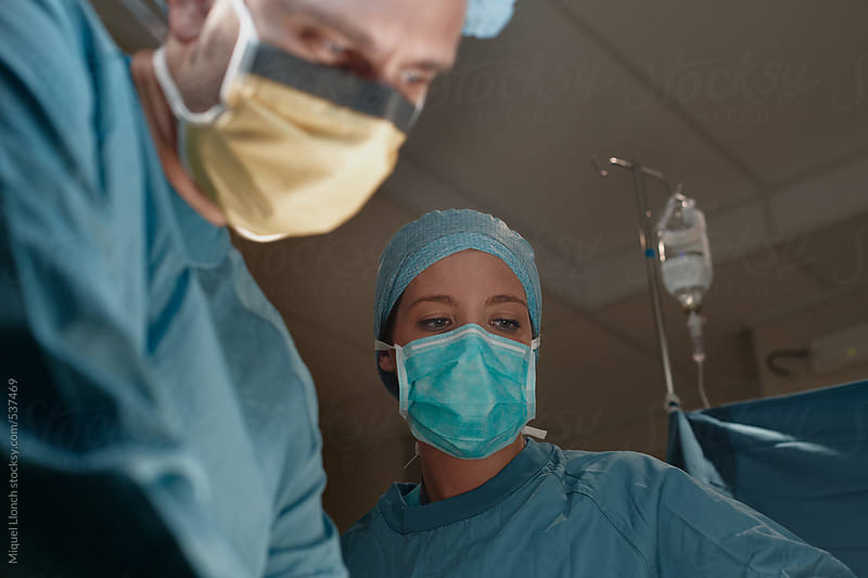 Close up portrait of two surgeons at work by Miquel Llonch for Stocksy United