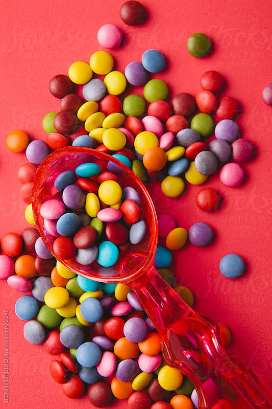 Close up of a pile of colorful chocolate coated candy with red spoon on red background. by BONNINSTUDIO for Stocksy United