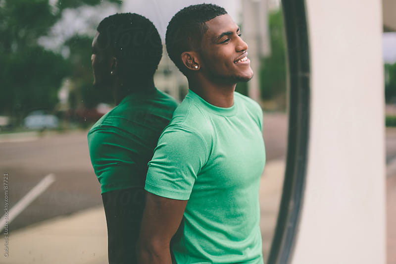 Black guy in front of window  by Gabrielle Lutze for Stocksy United