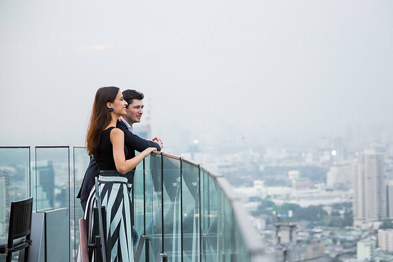 Stylish young couple enjoying the view in a modern rooftop bar by Jovo Jovanovic for Stocksy United