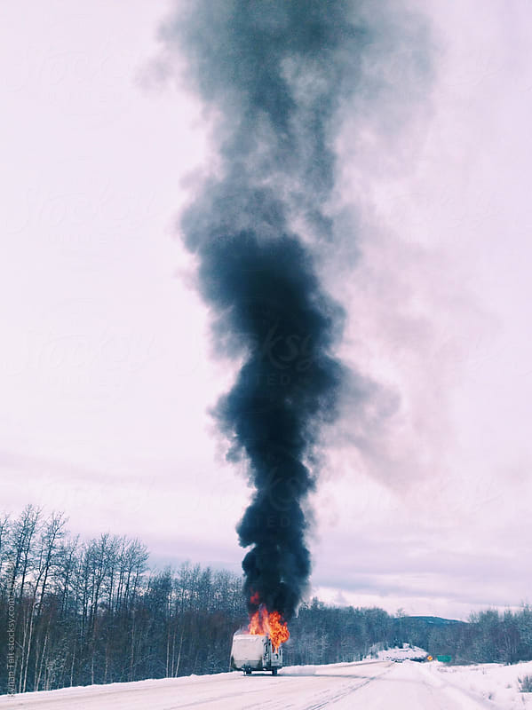 Trailer fire on a snowy highway by Kynan Tait for Stocksy United