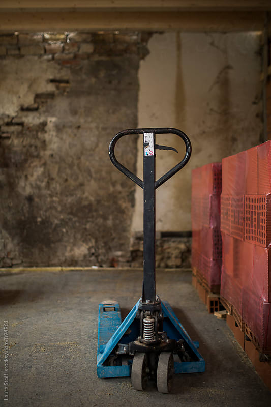 Pallet truck and clay bricks pile on pallets inside apartment under construction by Laura Stolfi for Stocksy United