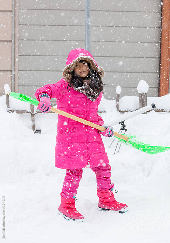 a girl cleaning snow outside house by jira Saki for Stocksy United