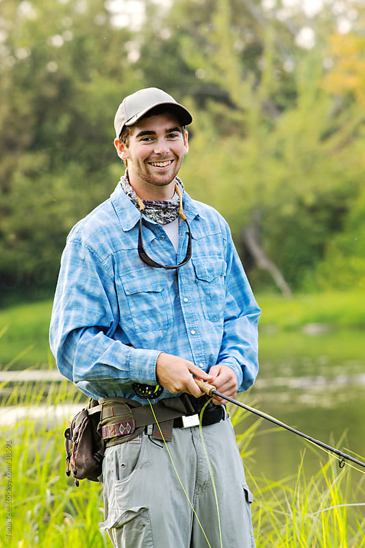 A young man holding his fly fishing rod.  by Tana Teel for Stocksy United