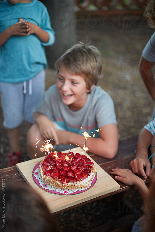Child and friends celebrating a birthday party by Miquel Llonch for Stocksy United