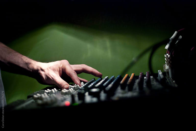 Sound guy turns the knobs at a live show by Cara Dolan for Stocksy United