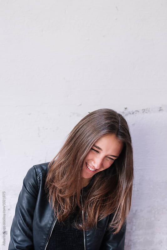 Smiling beautiful brunette against of white wall by Alberto Bogo for Stocksy United
