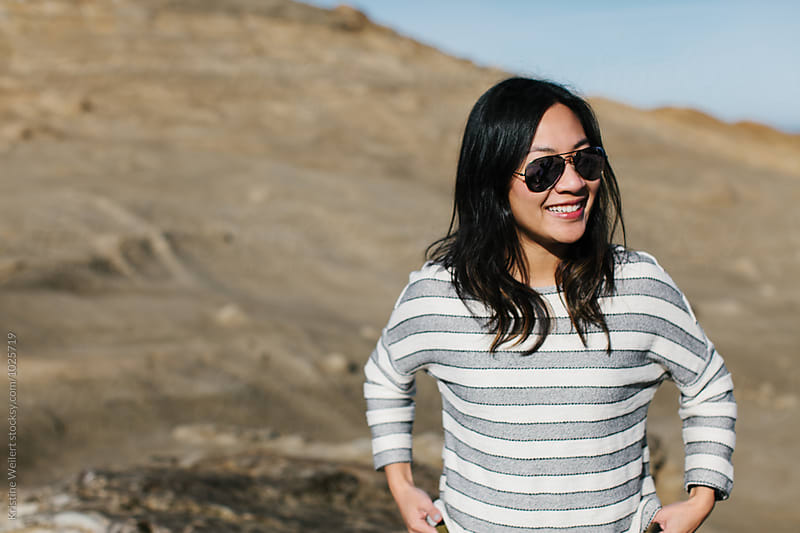 Vietnamese woman, wearing sunglasses outdoors by Kristine Weilert for Stocksy United