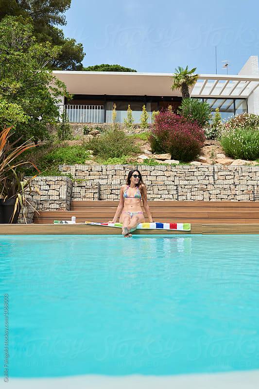 Smiling brunette in bikini at pool against of villa by Guille Faingold for Stocksy United