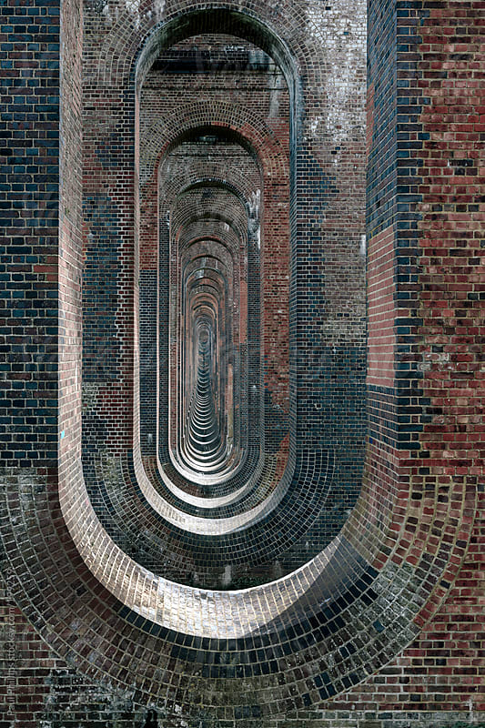 Receding interior arched columns of a railway viaduct by Paul Phillips for Stocksy United