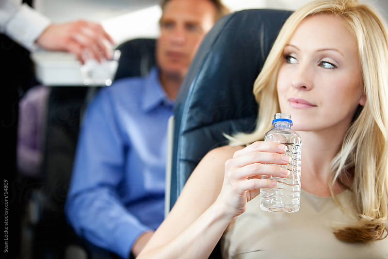 Airplane: Passenger Holds a Bottle of Water by Sean Locke for Stocksy United