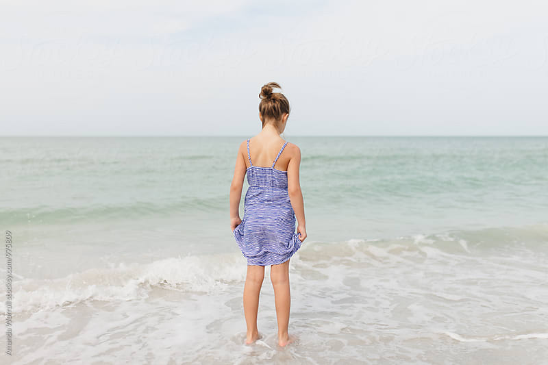 Preteen girl standing in the ocean, shot from behind by Amanda Worrall for Stocksy United