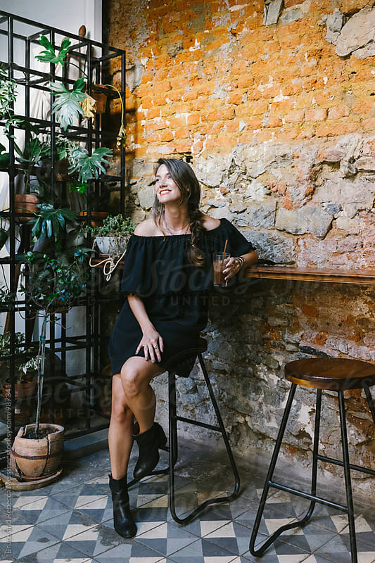 Woman in a bar by Bruce Meissner for Stocksy United