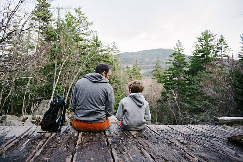 Father and son sit together by a mountain stream by Cara Dolan for Stocksy United