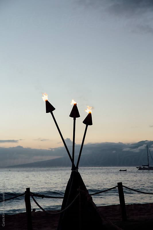 Hawaiian cone tiki torch with beautiful ocean background by Curtis Kim for Stocksy United