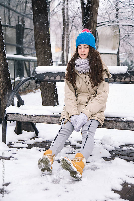 Young brunette woman sitting on bench in park by Danil Nevsky for Stocksy United
