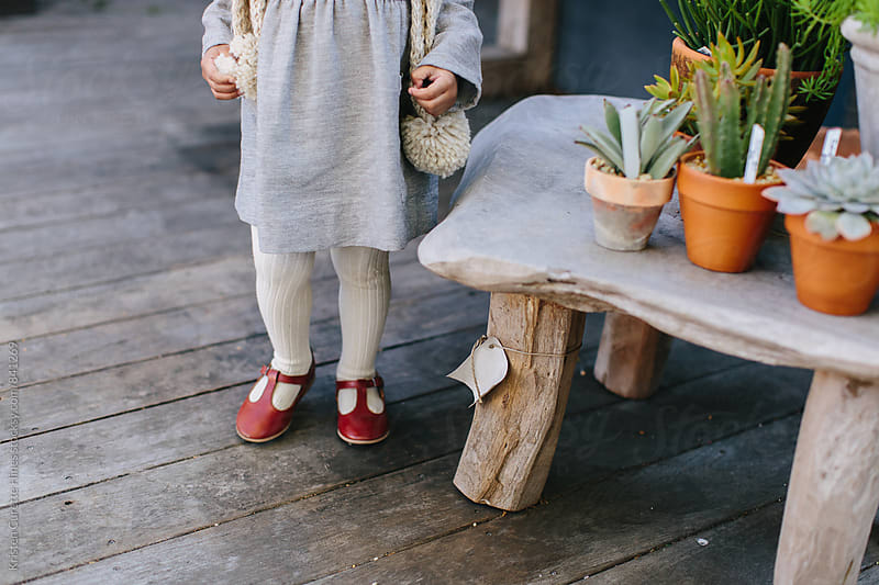 A little girl wearing dress shoes staning by miniature succulent plants by Kristen Curette Hines for Stocksy United