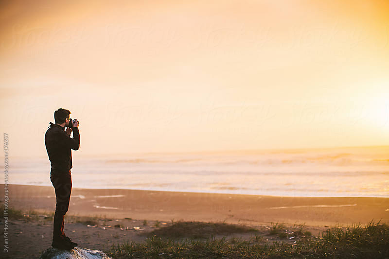 Man at the beach taking a photograph of the sunset by Dylan M Howell Photography for Stocksy United