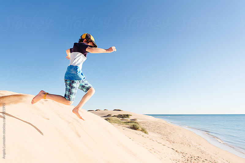 Boy leaping off large sand dunes at the Ningaloo Coast by Angela Lumsden for Stocksy United