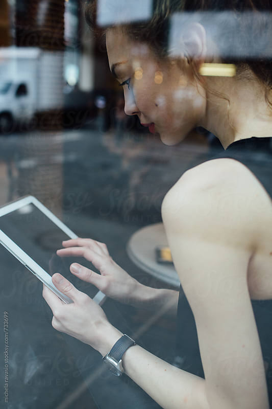 Businesswoman using digital tablet at cafe by michela ravasio for Stocksy United