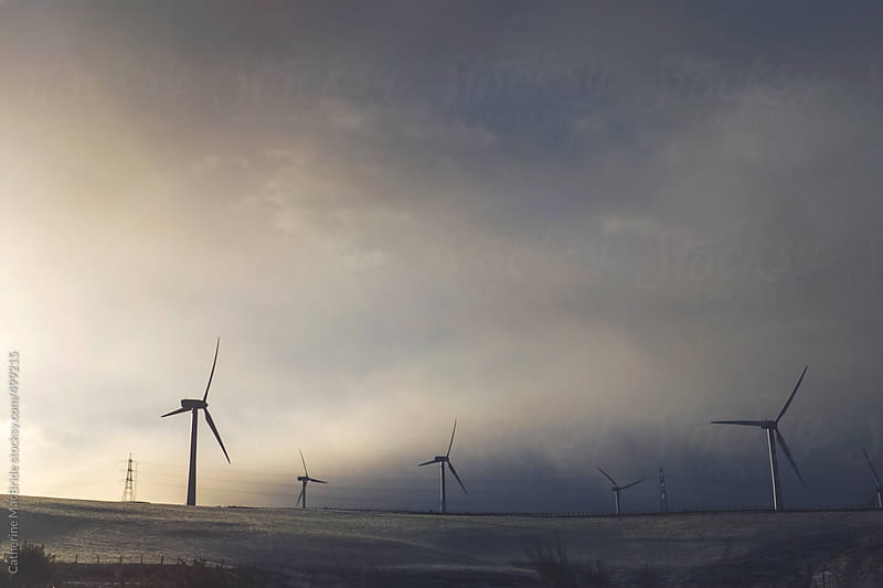 Wind turbines, pylons and snow clouds on the horizon...   by Catherine MacBride for Stocksy United
