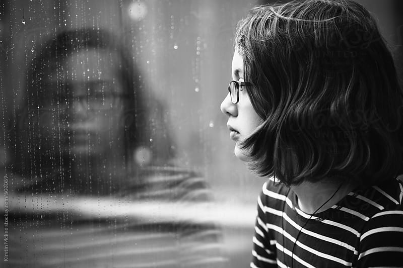 Girl looking out of window at the rain by Kirstin Mckee for Stocksy United