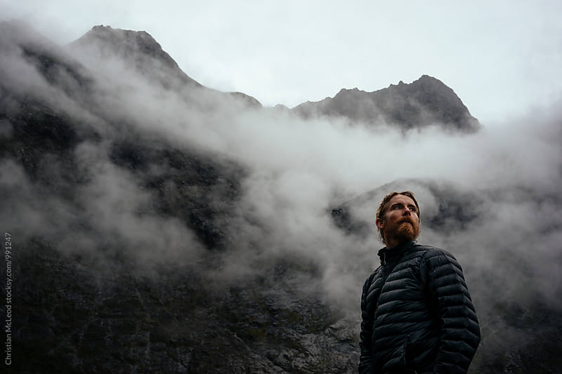 Man in his down jacket looking towards the cold foggy sky as the weather changes by Christian McLeod for Stocksy United