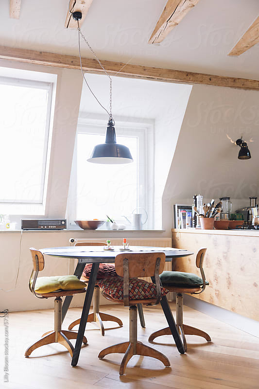 Dining area in a loft by Lilly Bloom for Stocksy United