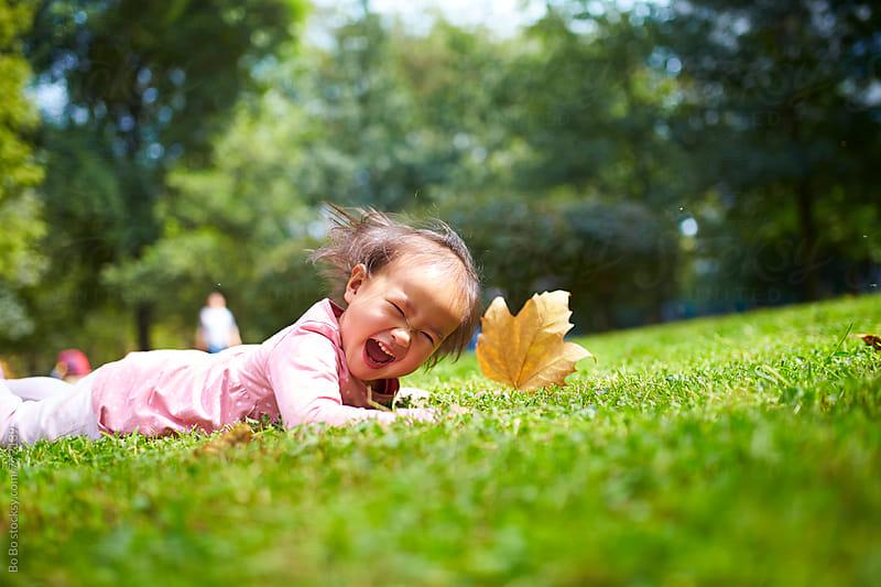 lovely little girl lying in lawn by Bo Bo for Stocksy United