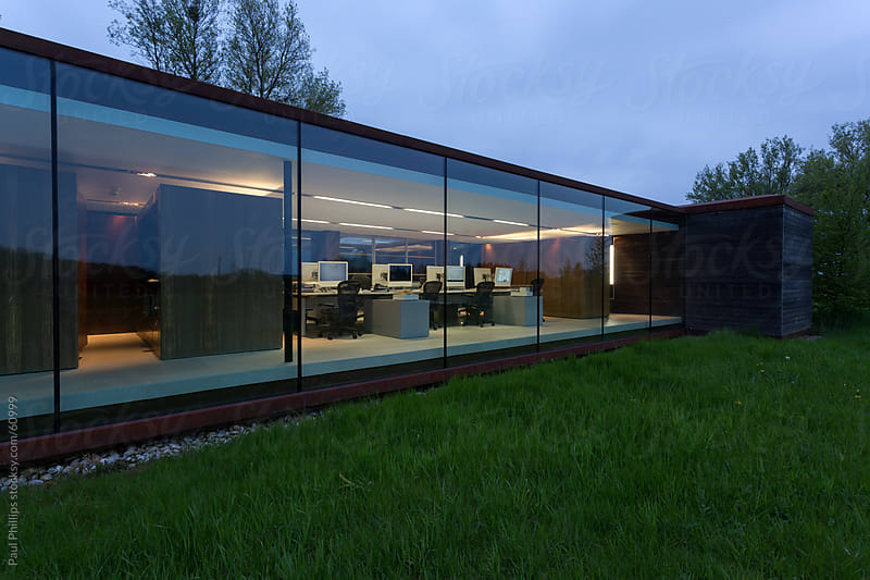 Glass facade of a modern office at twilight by Paul Phillips for Stocksy United