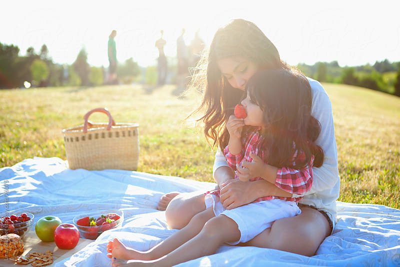 Mother and daughter eating fruit at summer picnic by Linzy Slusher for Stocksy United