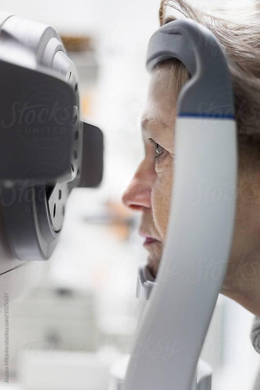 Senior woman at ophthalmology having eyes examination  by Jovana Milanko for Stocksy United