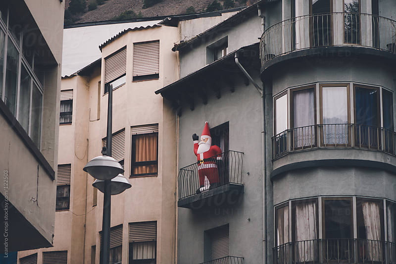 Inflatable Santa Claus figure salutes from balcony by Leandro Crespi for Stocksy United