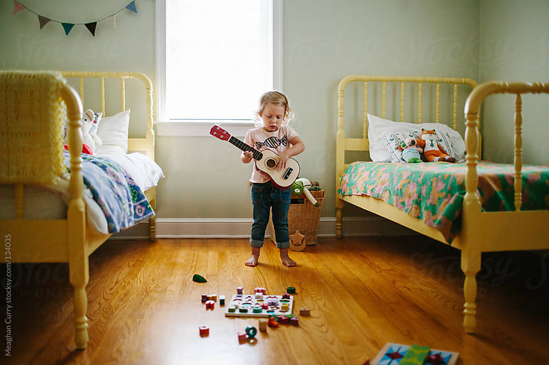 little girl playing the guitar in her bedroom by Meaghan Curry for Stocksy United