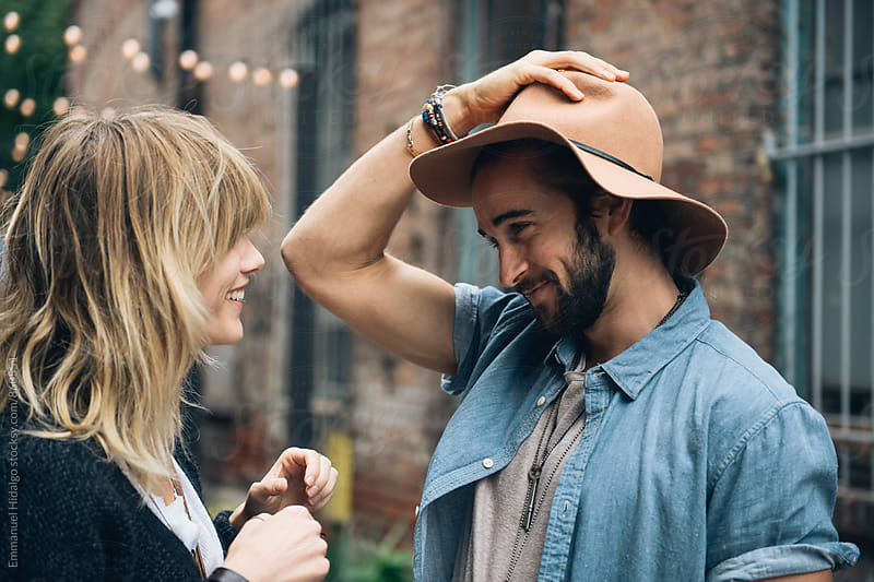 Man jokingly puts on his girlfriends hat by Emmanuel Hidalgo for Stocksy United