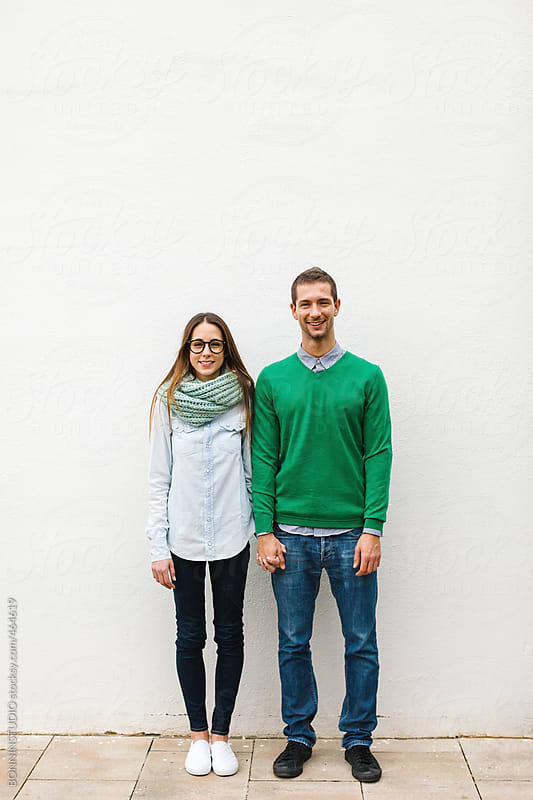 Portrait of young beautiful couple standing on white background. by BONNINSTUDIO for Stocksy United