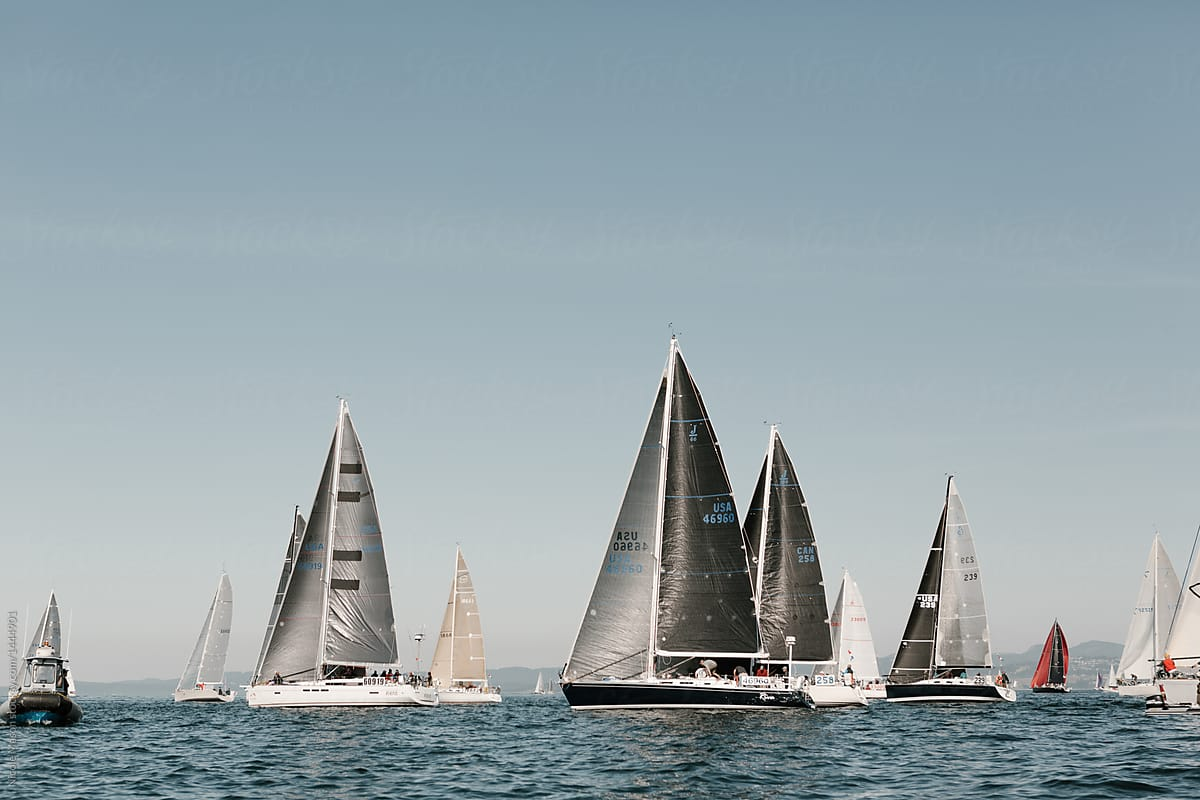 Stock Photo - Sailboats With Dark Sails Lining Up For Yacht Race To Begin