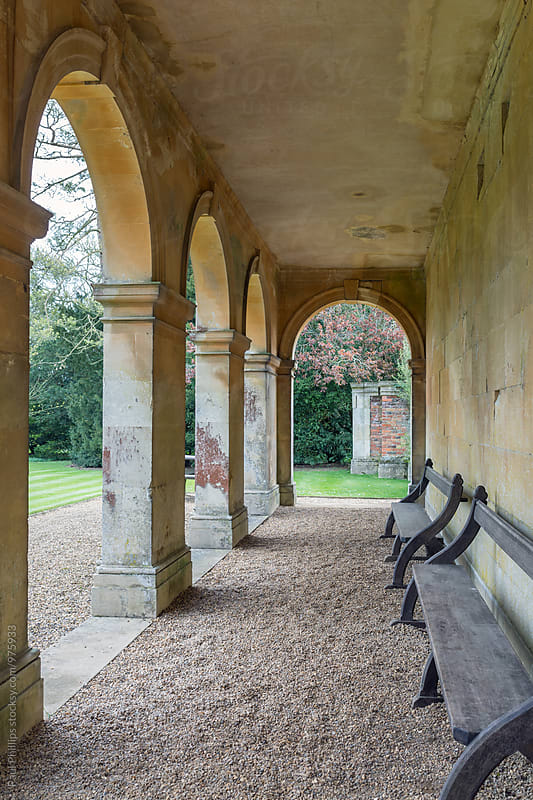 Stone arched walkway through a garden. by Paul Phillips for Stocksy United